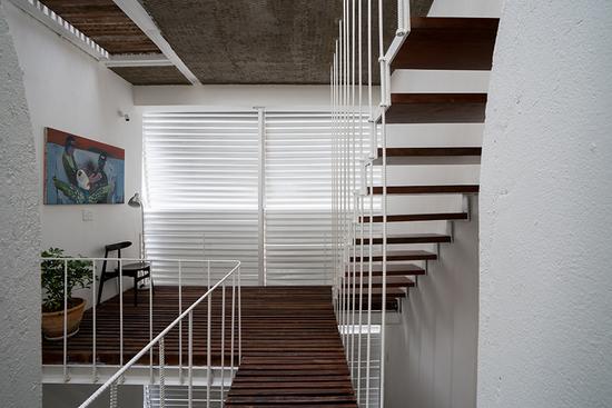 设计者利用木质楼板、百叶窗板和竹材图案天花板创造出别具一格的公共空间