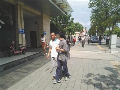 昨日上午10点40分,身穿白色T恤的缪新华及其家人走出法院。本版摄影/新京报记者 王�鹏程