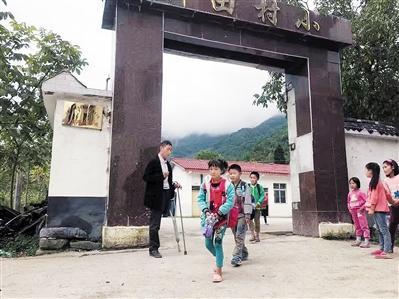 刘坤贤目送孩子们放学回家。(资料图)本报记者 张旭 摄