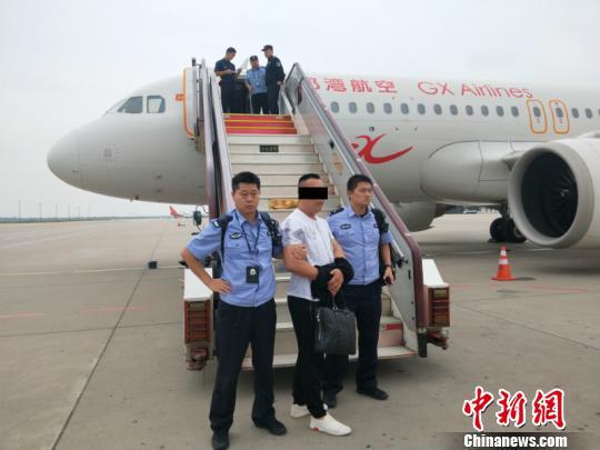 图为犯罪嫌疑人被押解回南宁 庞李柱 摄