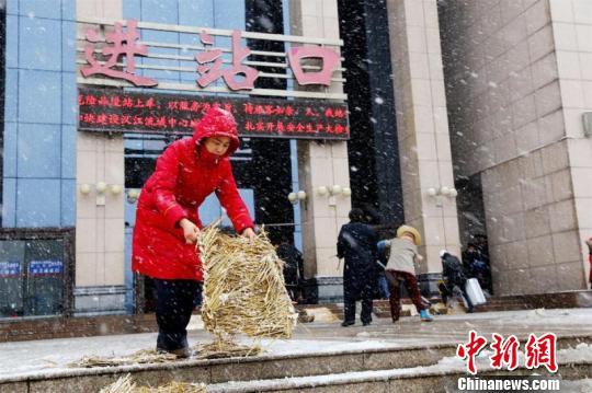 襄阳车站工作人员在进站口铺设防滑草垫。 高惠 摄