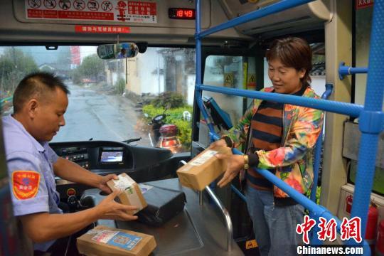 村民在公交车上领快递 罗伟 摄