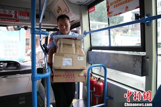 王付先提前将快递抱上公交车 胡传林 摄