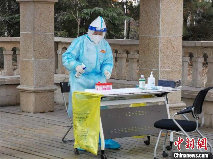 图为医务工作者在核酸检测前进行消毒工作。 屈冠华 摄