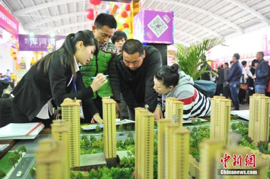资料图:辽宁省沈阳市,春季房交会现场,销售人员在给市民讲解。孙昊声 摄